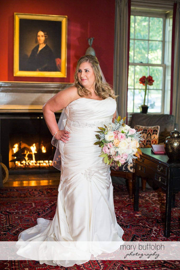 Bride stands in front of the fireplace at the Inns of Aurora Wedding