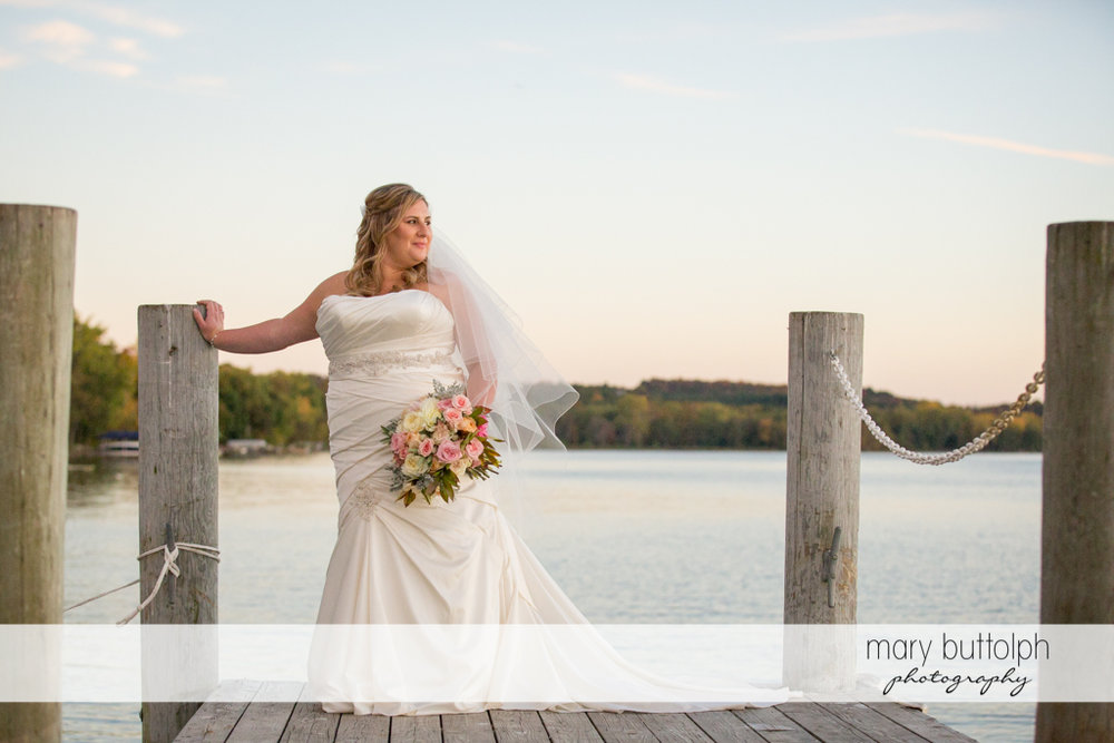 Bride stands by the lake at the Inns of Aurora Wedding