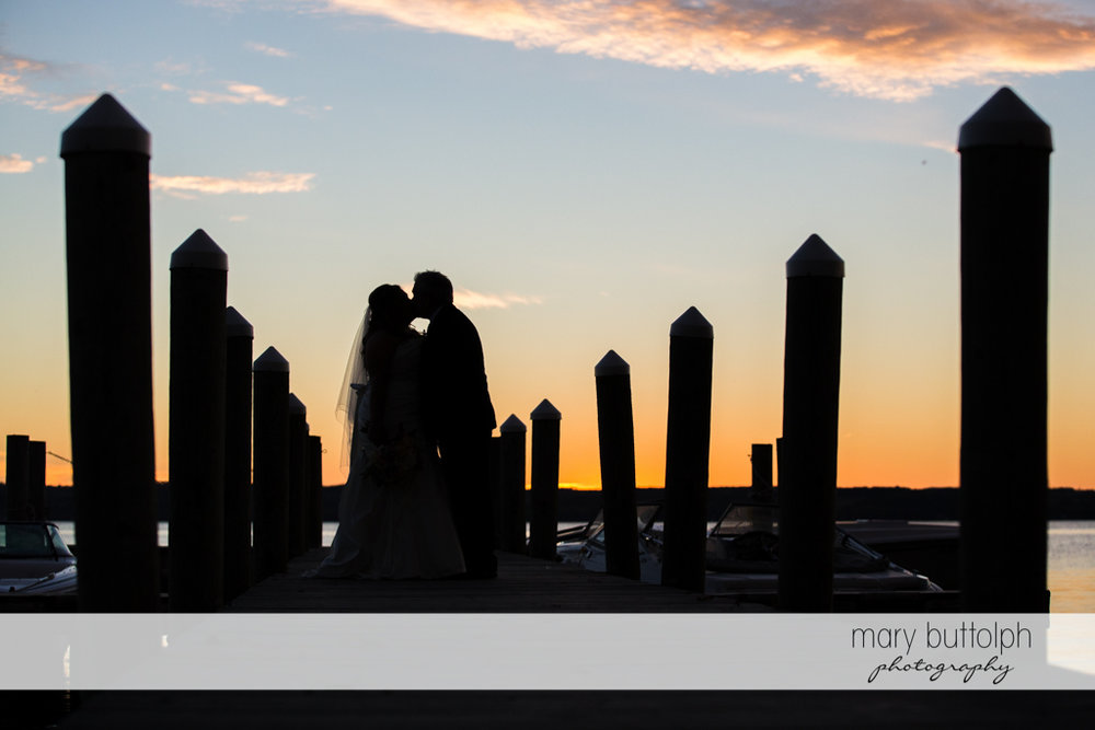 Couple kiss by the lake as the sun sets at the Inns of Aurora Wedding