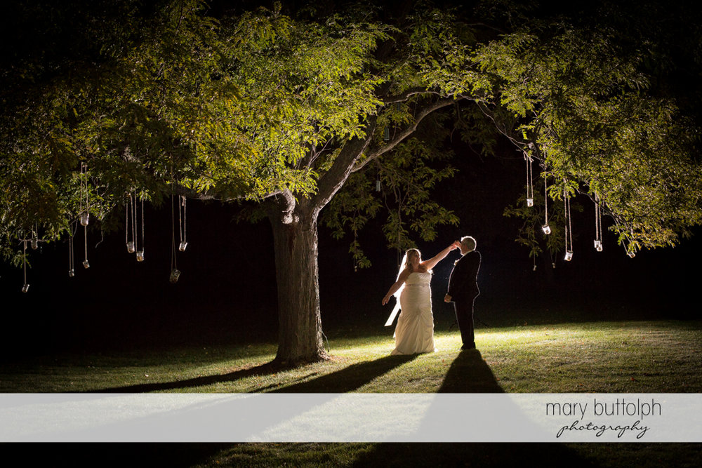 Couple dance in the moonlight under a tree at the Inns of Aurora Wedding