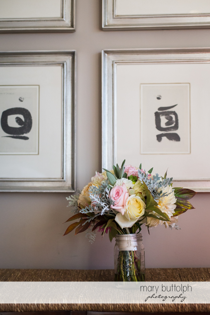 Bouquet in front of two paintings at the Inns of Aurora Wedding