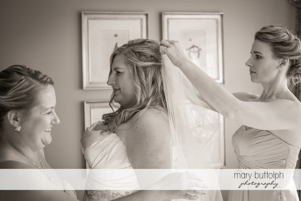 One of the bridesmaids attaches the bride's wedding veil at the Inns of Aurora Wedding