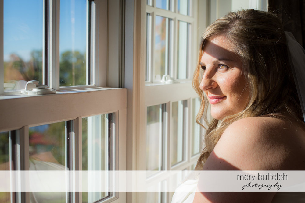 Bride looks through the window at the Inns of Aurora Wedding