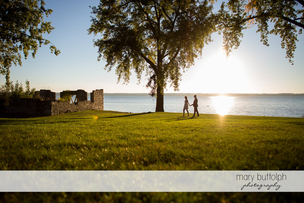 Couple relax by the lake near a brick structure at the Inns of Aurora Engagement