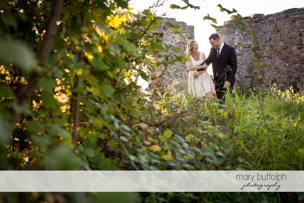 Couple stroll in the garden near a stone wall at the Inns of Aurora Engagement