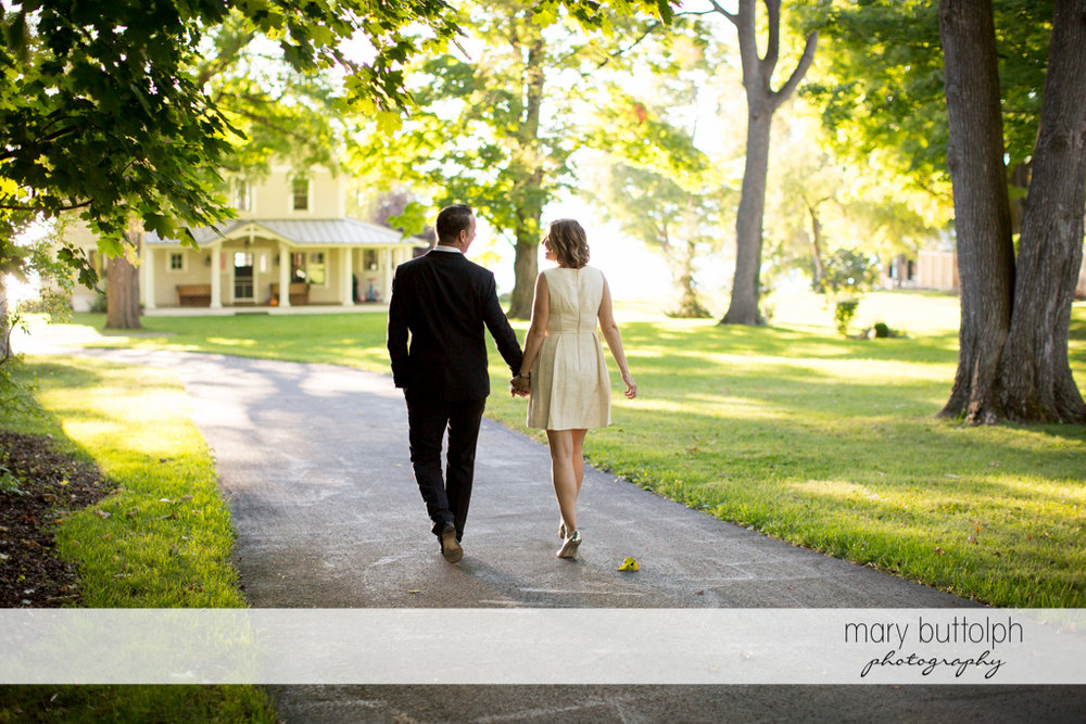 Couple walk to a house at the Inns of Aurora Engagement