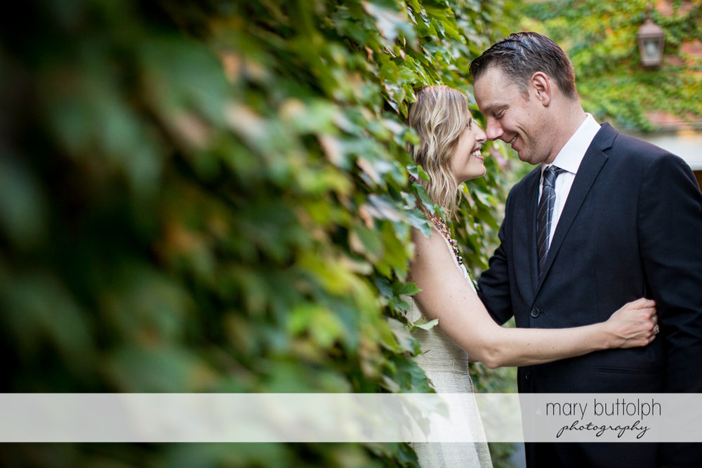 Couple pose near the plants in the garden at the Inns of Aurora Engagement