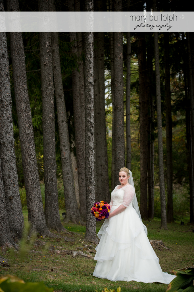 Bride with bouquet poses in the woods at Skaneateles Country Club Wedding