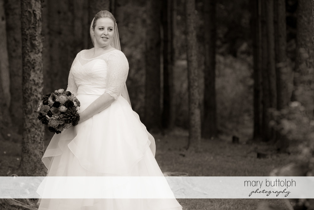 Dramatic black and white shot of the bride in the woods at Skaneateles Country Club