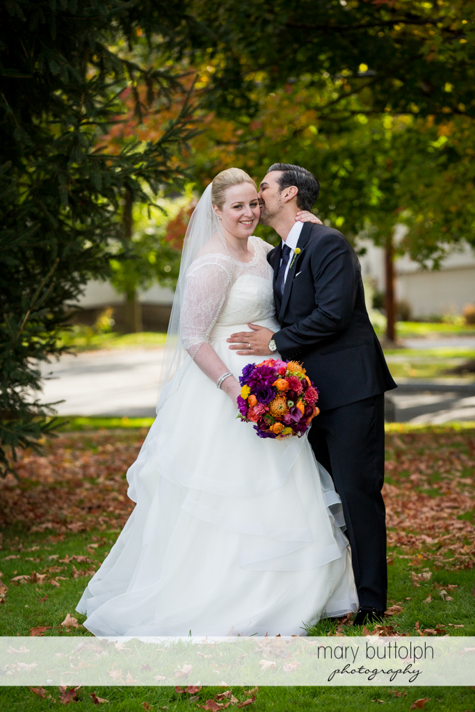 Couple share a tender moment in the garden at Skaneateles Country Club Wedding