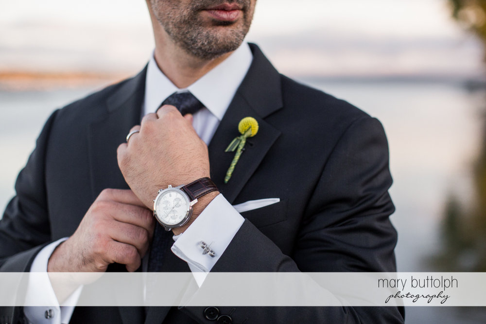 Close up shot of the groom's watch and corsage at Skaneateles Country Club Wedding
