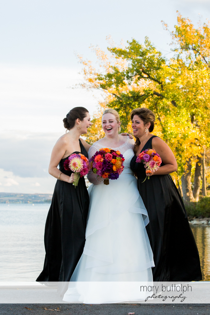 Bride and her bridesmaids near the lake at Skaneateles Country Club Wedding