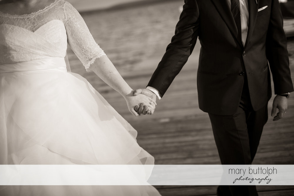 Couple hold hands near the lake at Skaneateles Country Club Wedding