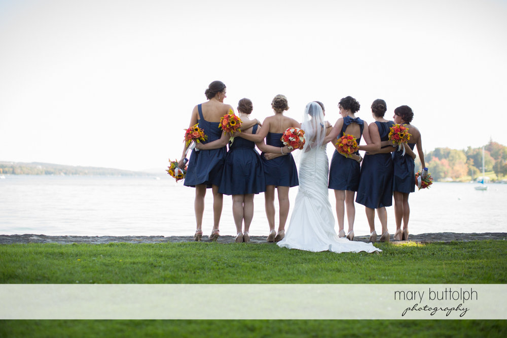 Bride and her bridesmaids face the lake at Skaneateles Country Club Wedding