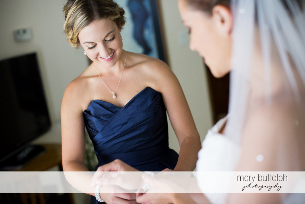 Bride helps a friend put on her bracelet at Skaneateles Country Club Wedding