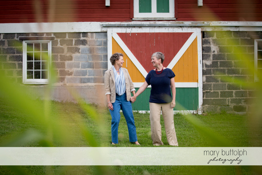 Same sex couple pose in front of an old house at Skaneateles Lake Engagement