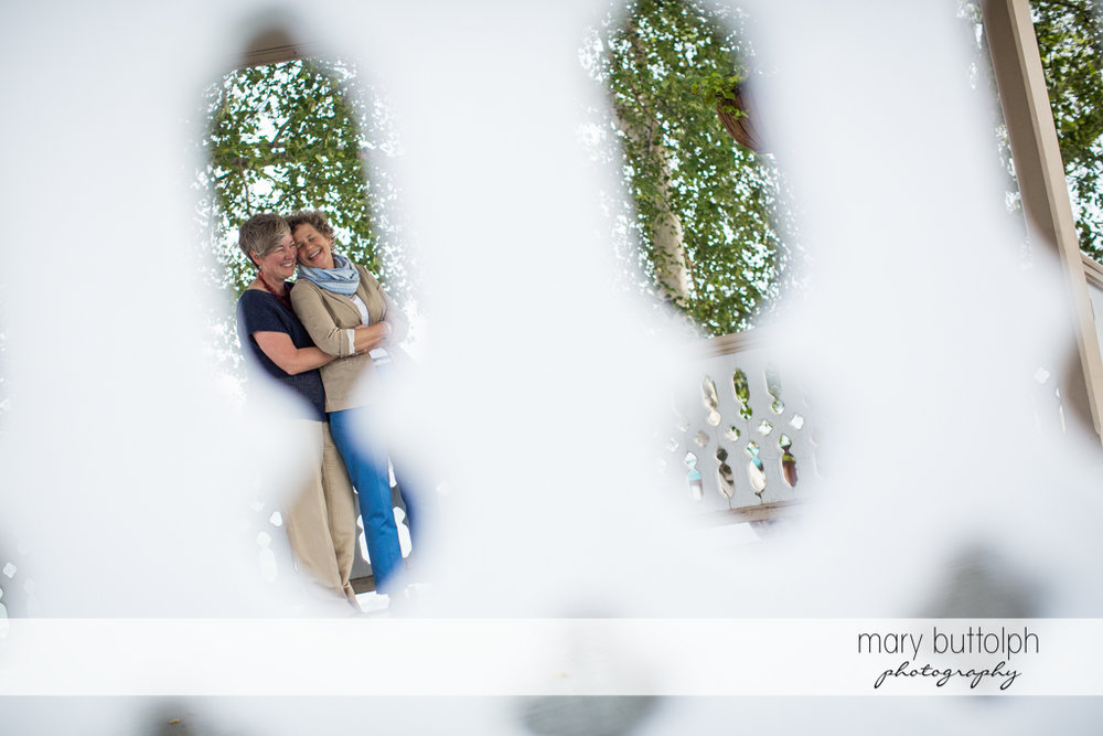 Same sex couple as seen through the fence at Skaneateles Lake Engagement