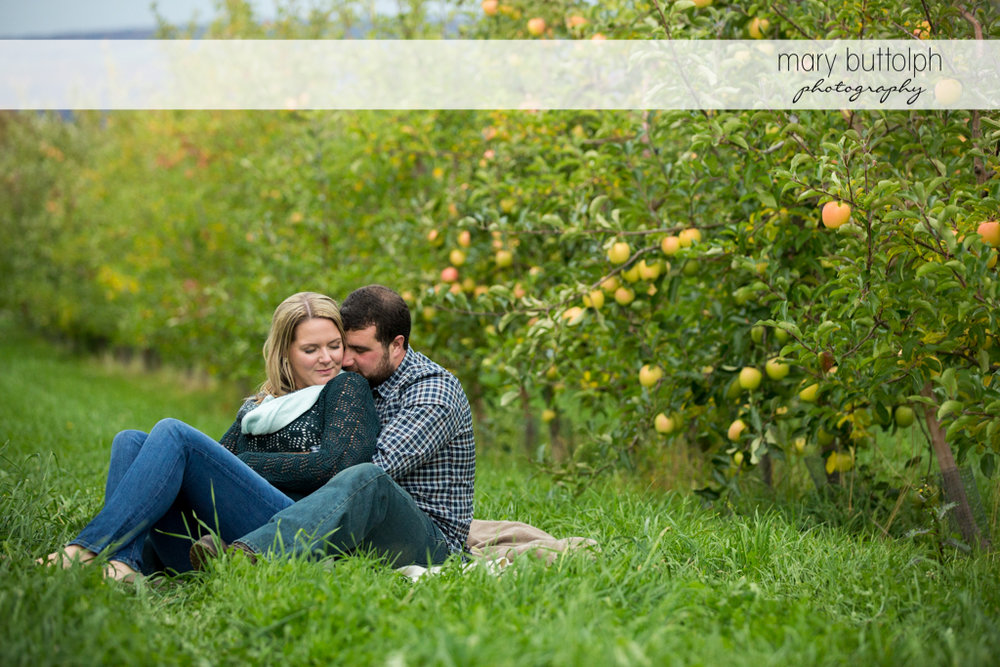 Couple relax in the garden near apples trees at Beak & Skiff Apple Orchards Engagement