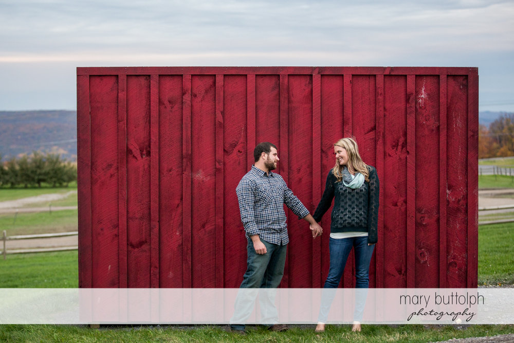 Couple hold hands in front of a wooden wall at Beak & Skiff Apple Orchards Engagement