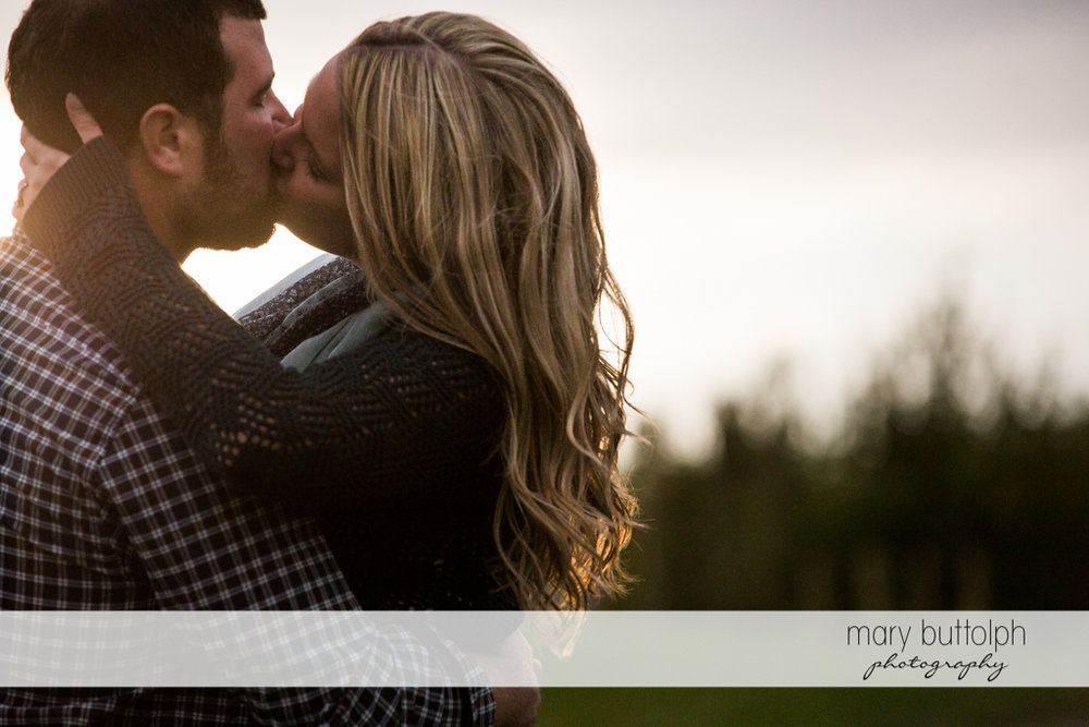 Couple kiss in the garden at Beak & Skiff Apple Orchards Engagement