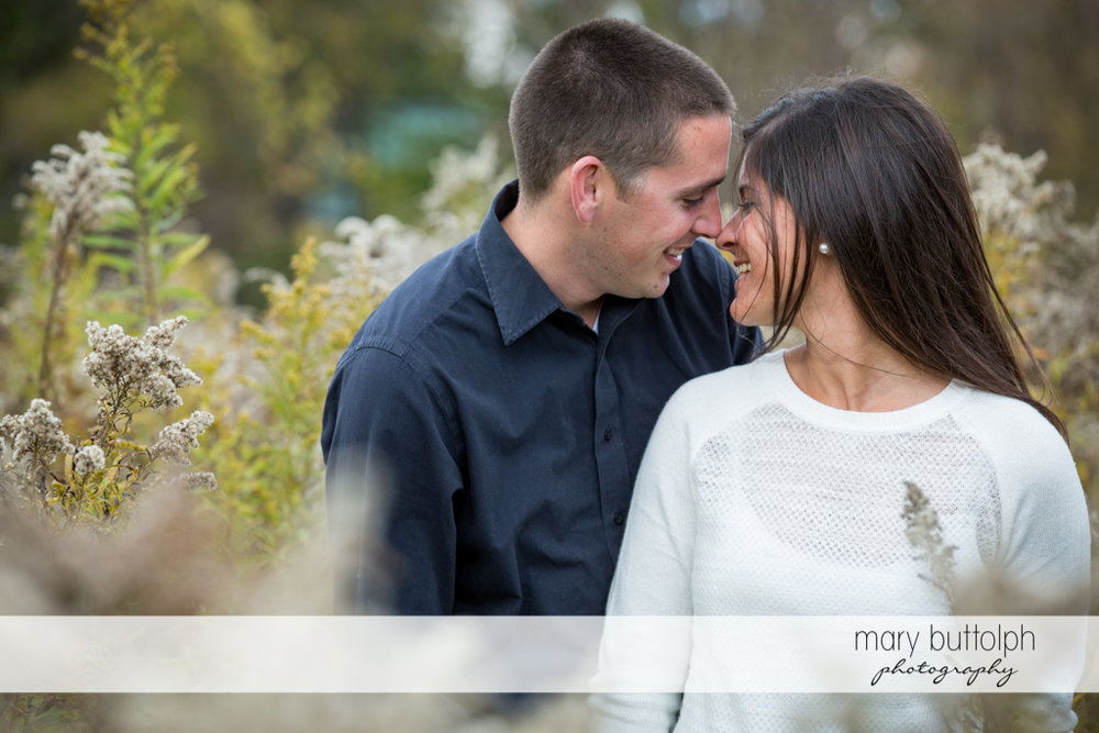 Couple rub noses in the garden at Skaneateles Lake Engagement