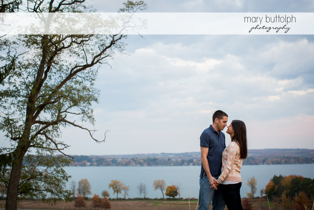 Couple hold hands near the lake at Skaneateles Lake Engagement