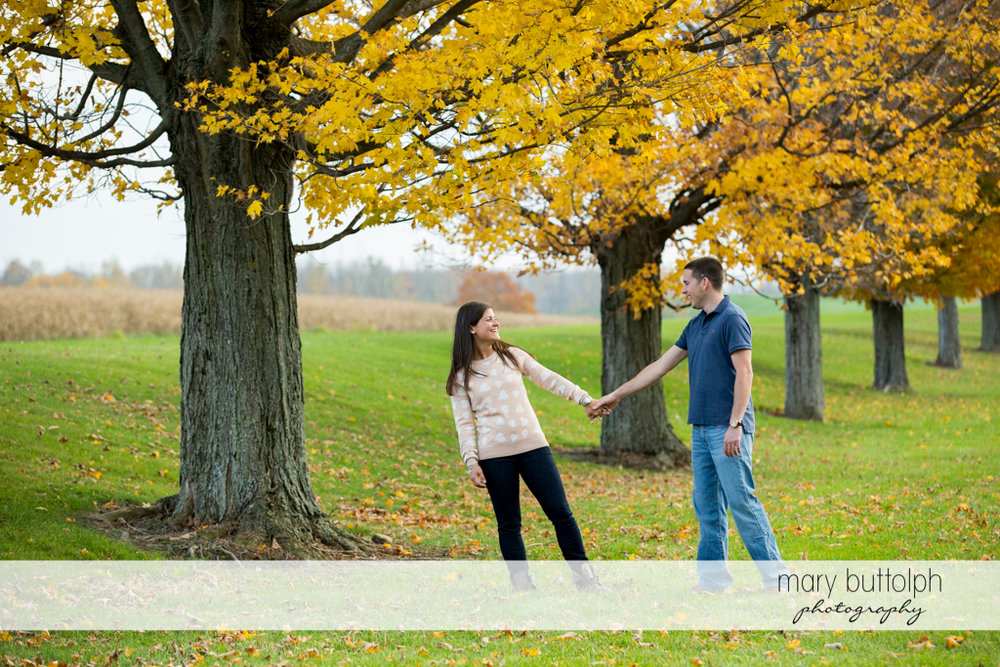 Couple hold hands in front of the trees in the garden at Skaneateles Lake Engagement