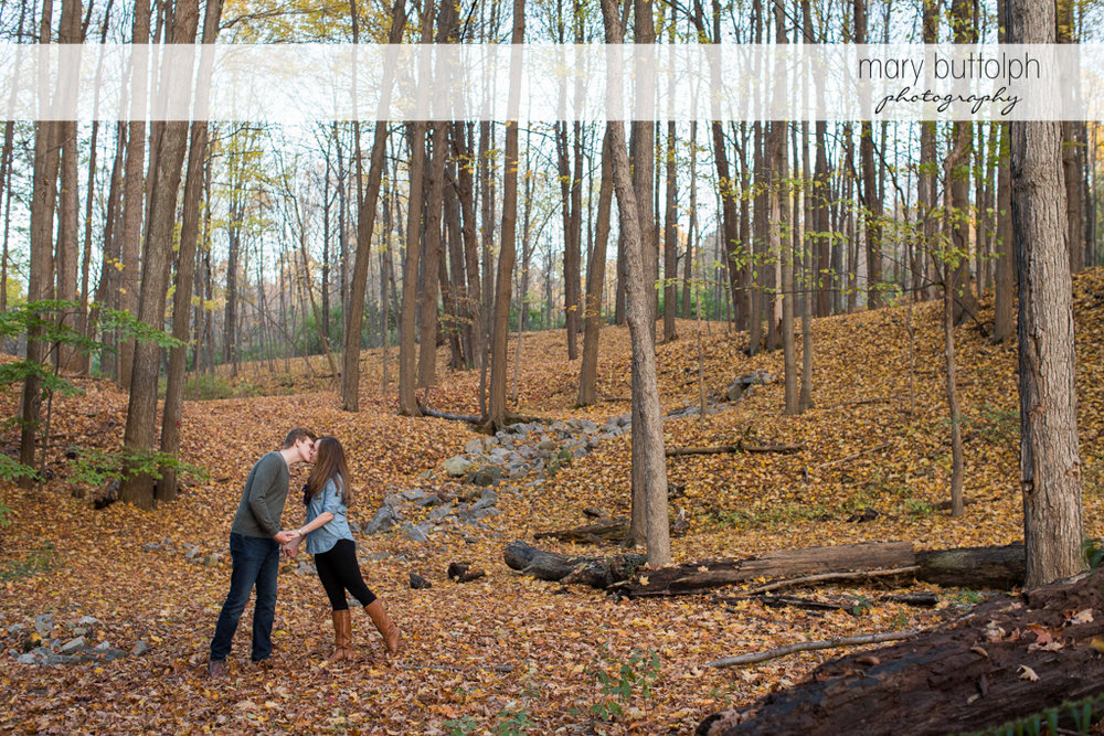 Couple kiss in the woods at Green Lakes Engagement
