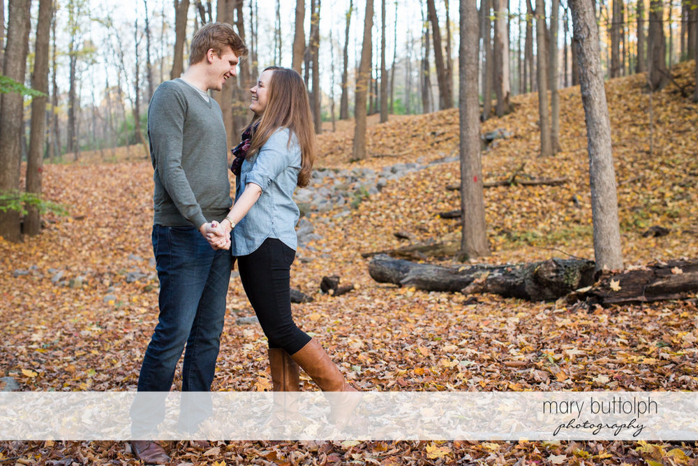 Couple hold hands in the woods at Green Lakes Engagement