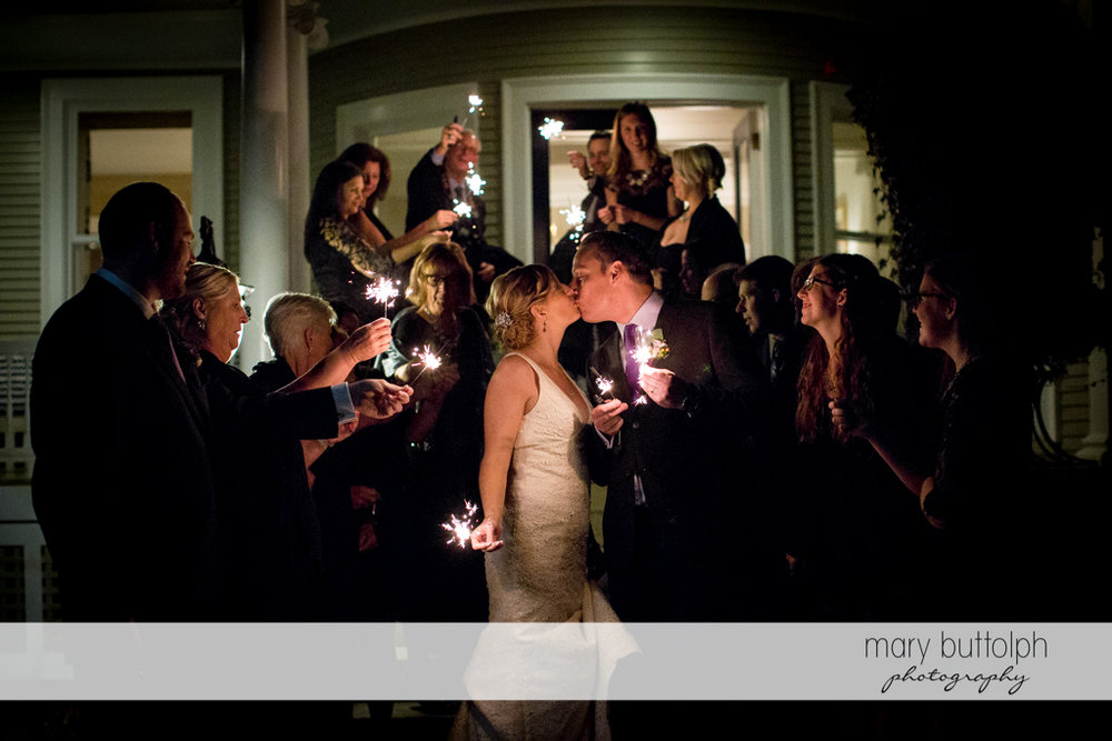 Sparklers light up the night as the couple kiss in front of guests at Rowland House Wedding