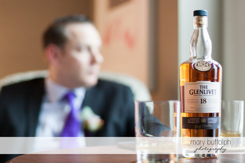 Groom sits in front of a bottle of whisky at Rowland House Wedding