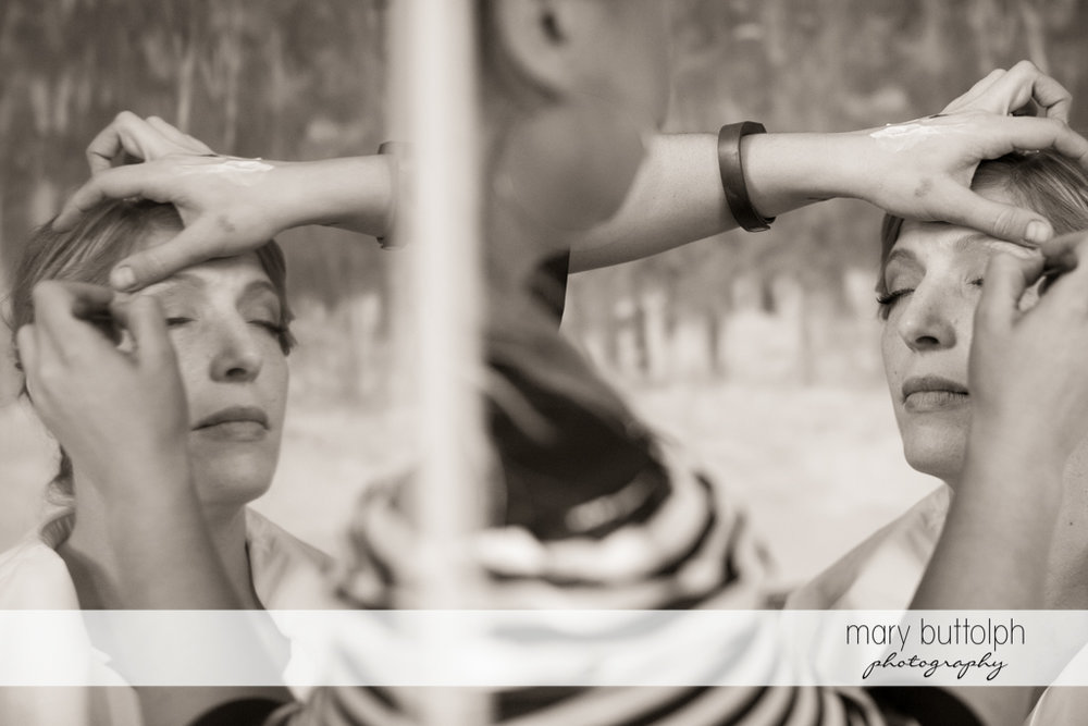Bride's reflection appears in the mirror as she gets a makeover at Rowland House Wedding