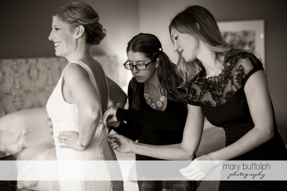 Bride slips on her wedding dress with a little from her friends at Rowland House Wedding