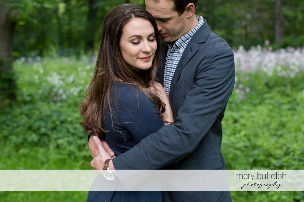 Couple show affection in the park at Skaneateles Lake Engagement