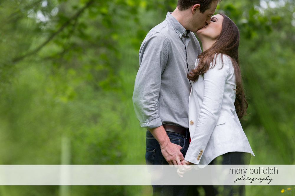 Couple kiss in the park at Skaneateles Lake Engagement