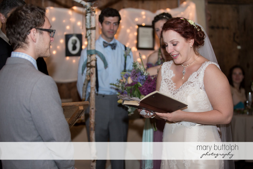 Bride reads from a book as the groom watches at Frog Pond Bed & Breakfast Wedding