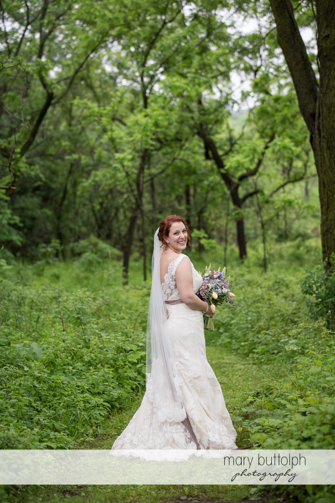 Bride with bouquet poses in the garden at Frog Pond Bed & Breakfast Wedding