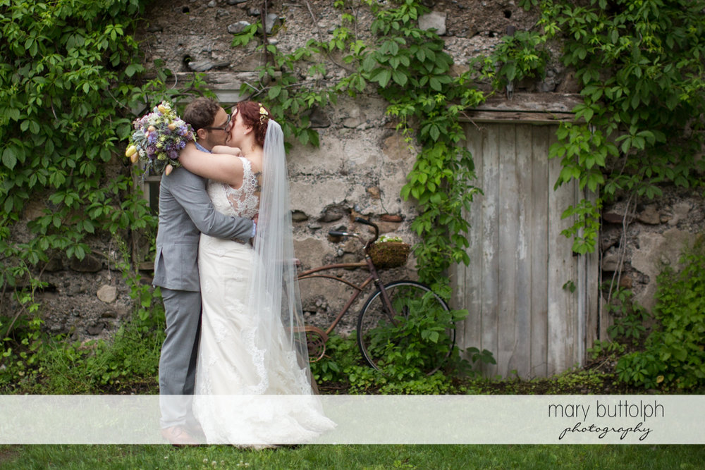 Couple kiss near an old stone house at Frog Pond Bed & Breakfast Wedding