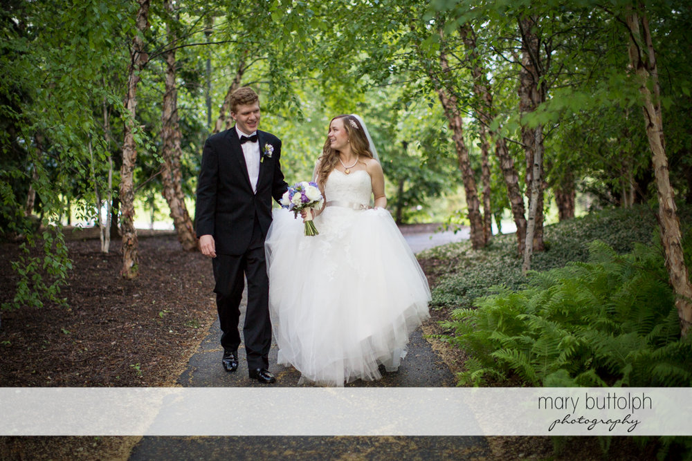 Couple stroll along the walkway in the garden at the Lodge at Welch Allyn Wedding