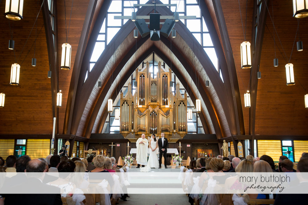 Couple pose with the priest in front of the altar at the Lodge at Welch Allyn Wedding
