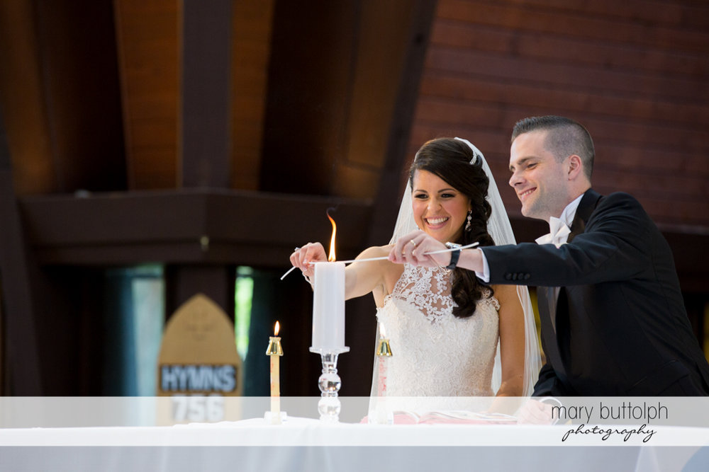 Couple light the candle in front of the altar at the Lodge at Welch Allyn Wedding