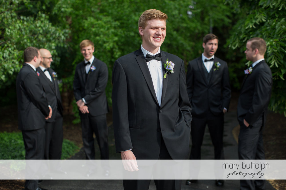 Groom poses in front of the groomsmen in the garden at the Lodge at Welch Allyn Wedding