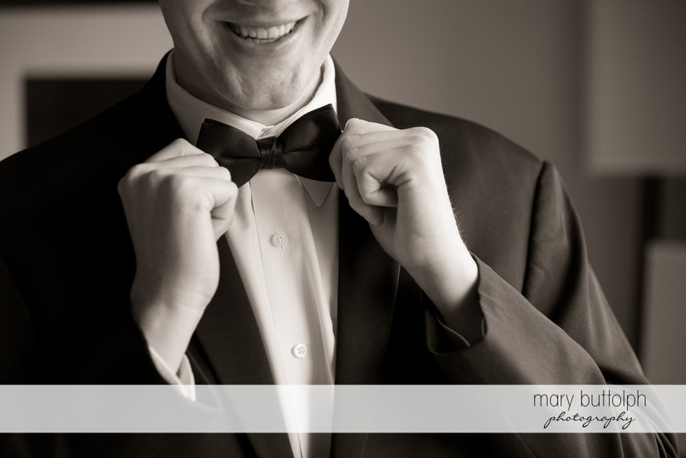 Groom smiles as he fixes his tie at the Lodge at Welch Allyn Wedding