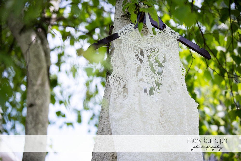 Bride's wedding dress hangs from a tree at the Lodge at Welch Allyn Wedding