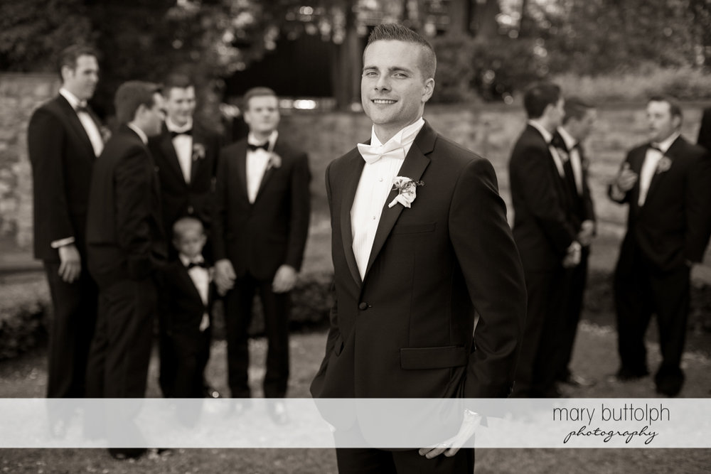 Groom poses in front of his groomsmen at the Lodge at Welch Allyn Wedding