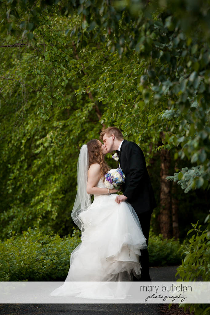 Couple kiss in the woods at the Lodge at Welch Allyn Wedding
