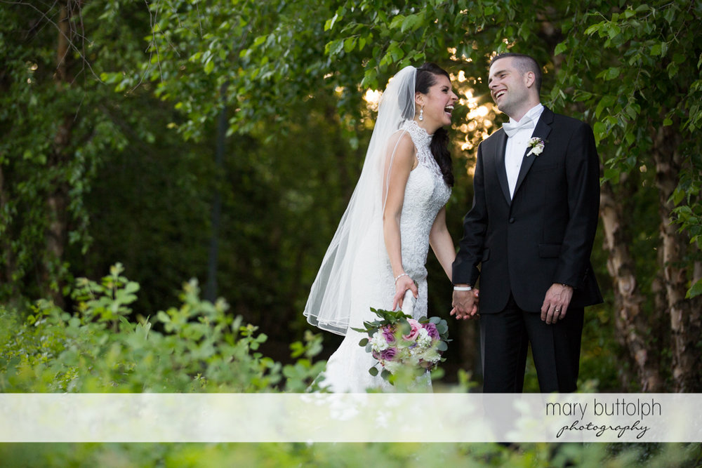 Couple find something funny in the garden at the Lodge at Welch Allyn Wedding