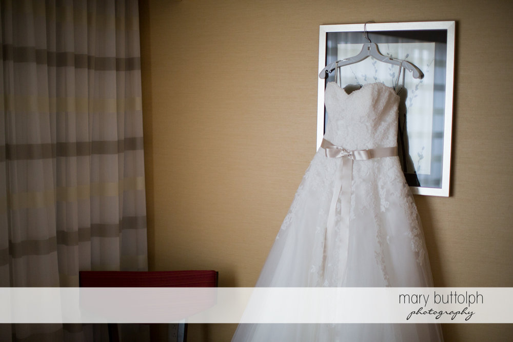Bride's wedding gown hangs on the wall at the Lodge at Welch Allyn Wedding