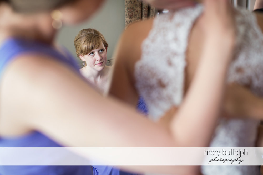 Bride's mother looks at her daughter as she puts on her wedding dress at the Lodge at Welch Allyn Wedding