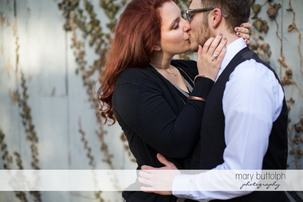 Couple kiss in front of a wooden wall at Skaneateles Engagement